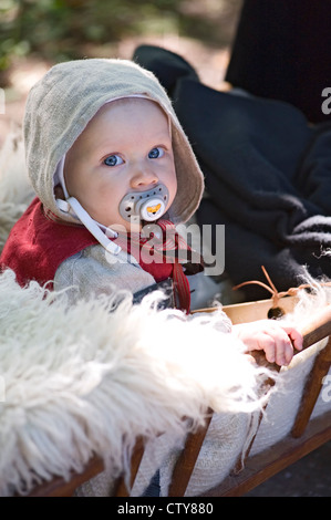 Little baby in medieval mask at festival - Stock Photo