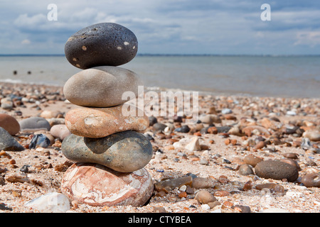 A tower built of pebbles on a beach - Stock Photo