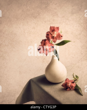 Flowers in vase on side table with textured effect - Stock Photo