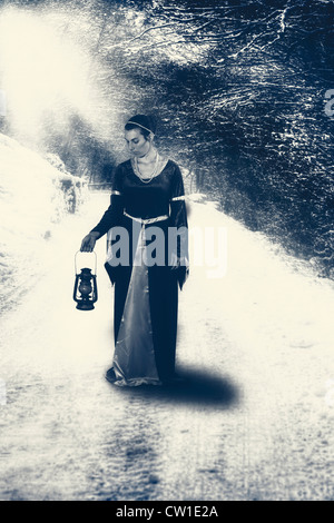 a woman is walking on a lonely street in winter - Stock Photo