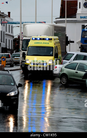 Ambulance in town centre in wet weather - Stock Photo