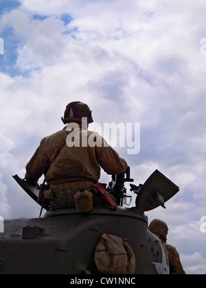 Portrait close up of tank commander aiming machine gun on American Sherman Tank at Military Vehicle show in Essex - Stock Photo