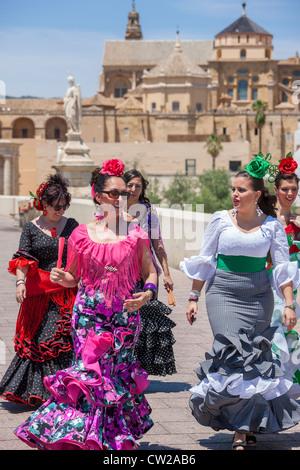 Cordoba Roman Bridge. Women going to the May Feria festival, dressed in traditional Spanish Traje de Gitana, or - Stock Photo