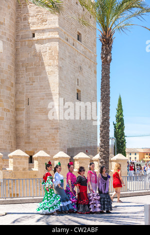 Calahorra Tower in Cordoba Spain. Women posing dressed in traditional Spanish flamenco dresses for the May Feria - Stock Photo