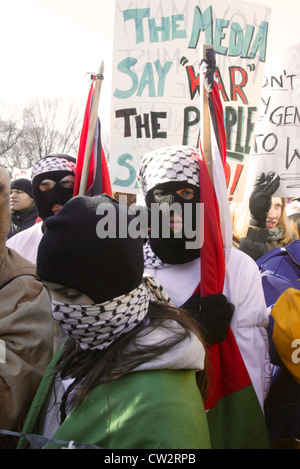 Protesters with covered faces during a large anti war rally leading up to the Iraq war on the National Mall in Washington - Stock Photo