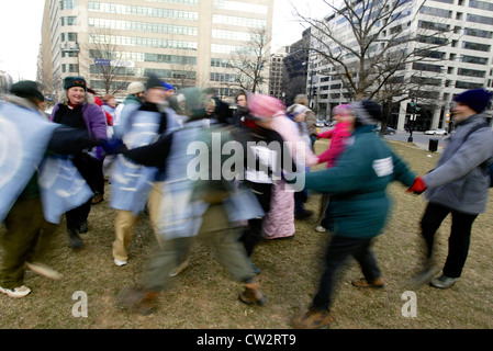 Anti war protesters dance in a circle during a large anti war rally leading up to the Iraq war in Washington DC - Stock Photo