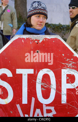 A protester holds up a sign reading 'Stop War', during a large anti war rally leading up to the Iraq war on the - Stock Photo