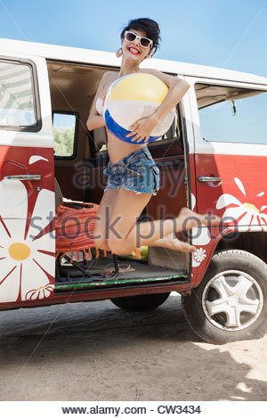 Young woman jumping with beach ball - Stock Photo