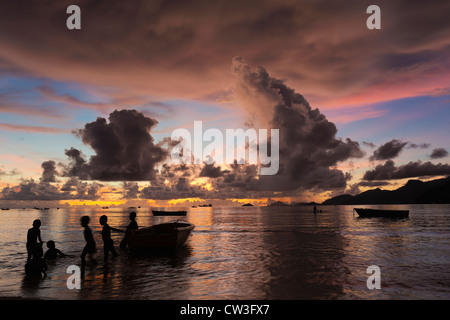 Fishing boats with children at sunset on a secluded beach. Mahe Seychelles - Stock Photo