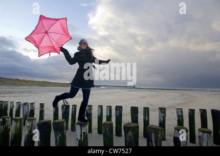 young woman with pink umbrella balancing on spur dikes, Netherlands, Zeeland, Breskens - Stock Photo