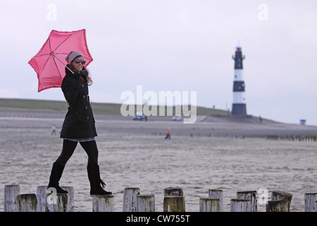 young woman with pink umbrella balancing on spur dikes with lighthouse in the background, Netherlands, Zeeland, - Stock Photo