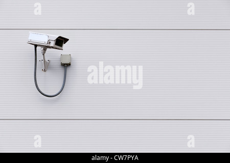 Photo of a CCTV security camera on the wall of a building with copy space for text. - Stock Photo