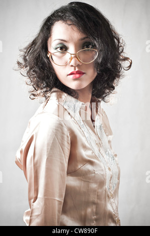 Portrait of a curly-haired Asian girl with glasses, picture taken in a studio room. - Stock Photo