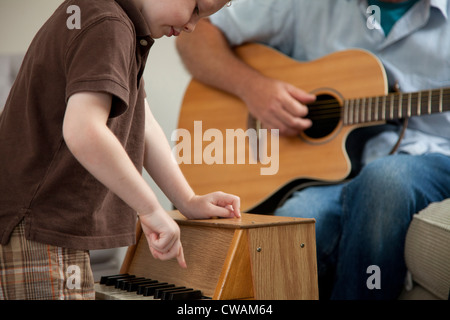 Boy playing little piano as man plays guitar - Stock Photo