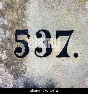 house number five hundred and thirty-seven, painted on a cement wall - Stock Photo