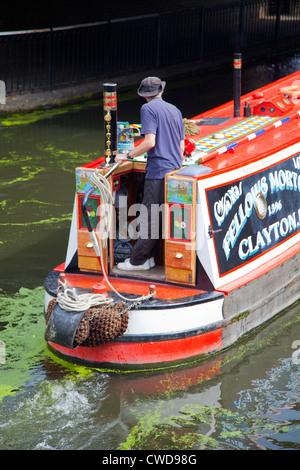 Man on Barge navigating Regents Canal through Camden Lock in London UK - Stock Photo
