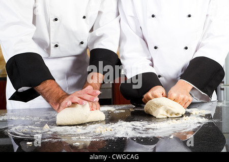 professional chef hands kneading bread dough on kitchen counter - Stock Photo