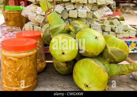 Horizontal close up of tubs of palm sugar, fresh coconuts and the tubes of prepared palm sugar sweets ready to sell - Stock Photo