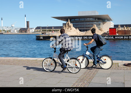 Two male tourists cycling along the quayside at Larsens Plads on the free city bikes looking at sand sculptures - Stock Photo