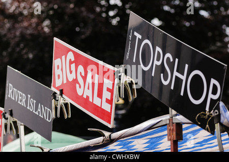 Signs advertising counterfeit products from River Island and Top shop at a market stall - Stock Photo
