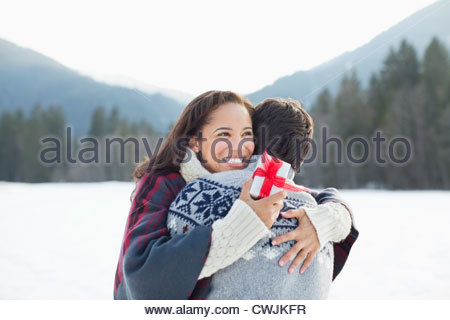Smiling woman holding Christmas gift and hugging man in snow - Stock Photo