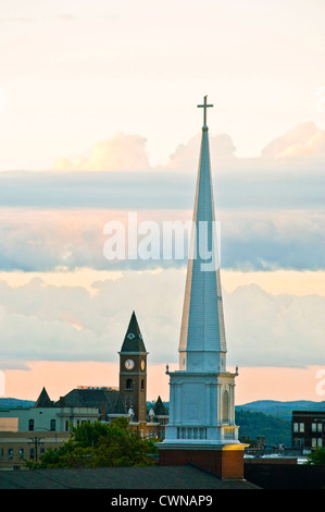 A church steeple and courthouse steeple at sunrise in Fayetteville, Arkansas. - Stock Photo