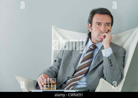 Mature businessman relaxing with drink and cigar - Stock Photo