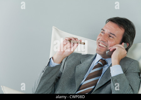 Mature businessman using cell phone and smoking cigar - Stock Photo