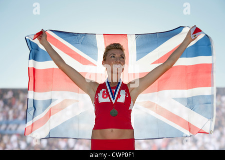 Young female medalist holding up British flag - Stock Photo