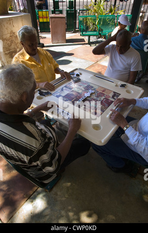 SENIOR MEN SITTING PLAYING DOMINOS DOMINO PARK CALLE OCHO LITTLE HAVANA MIAMI FLORIDA USA - Stock Photo