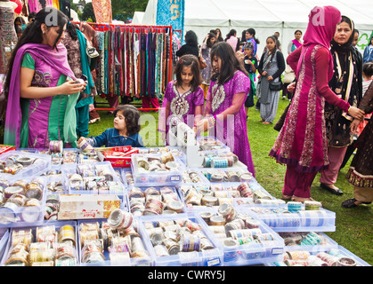 South Asian woman examining bangles for sale at the bazaar market at Edinburgh Mela, a multicultural festival held - Stock Photo