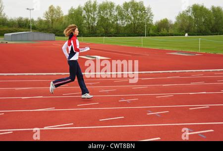 Female athlete running on athletic track - Stock Photo