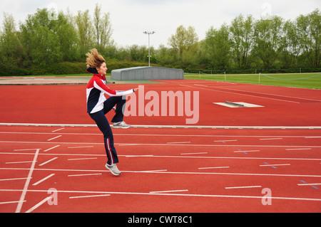 Female athlete doing exercise, drills, training on the athletic track - Stock Photo