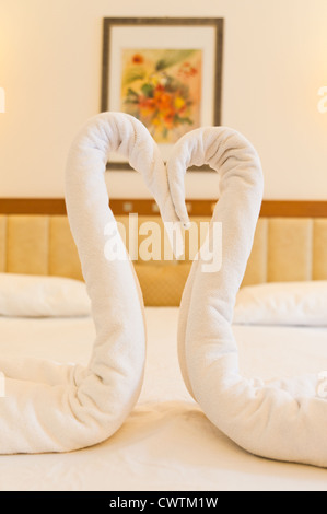 A couple of fake swan made of towel on the hotel bed - Stock Photo