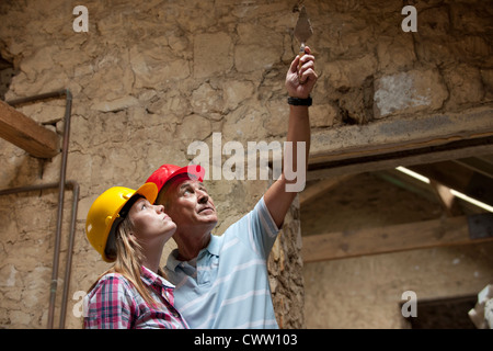 Construction workers examining stone - Stock Photo