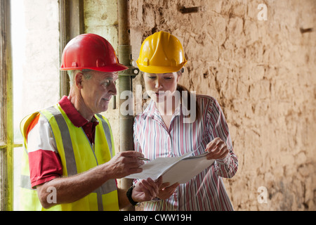 Construction workers examining papers - Stock Photo