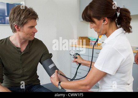 Doctor taking patients blood pressure - Stock Photo
