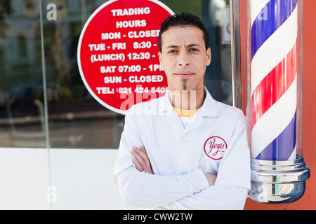 Barber standing outside shop - Stock Photo
