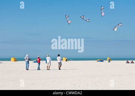 Four men demonstrate syncronized flying on St. Pete Beach at the Treasure Island Kite Festival in Treasure Island, - Stock Photo