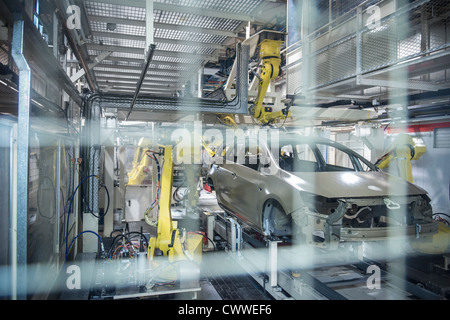 Robots applying sealant to cars in car factory - Stock Photo