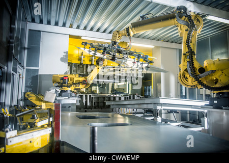 Car parts handled by robots in car factory - Stock Photo