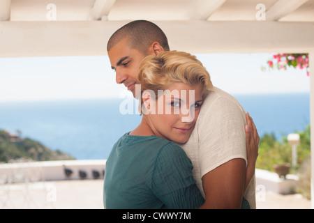 Smiling couple hugging on balcony - Stock Photo
