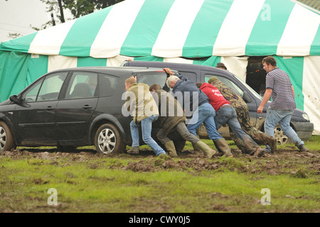 pushing a car stuck in mud - Stock Photo