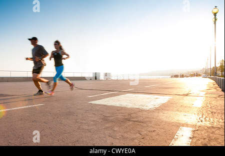 Man and woman running on the promenade at the seaside. Motion blur on the runners, a lot of copy space (Nice, France, - Stock Photo