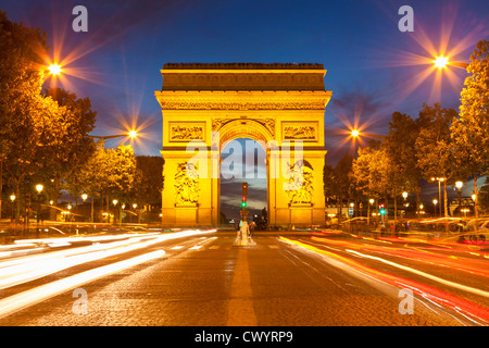 arc du triomphe and Champs Elysees traffic light trails at night Paris France EU Europe - Stock Photo