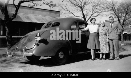 A family standing next to their American car in Bulawayo, Zimbabwe, in the 1940s. - Stock Photo