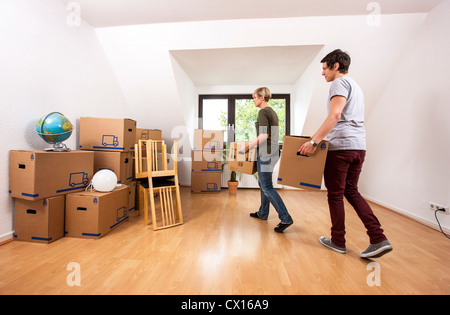 Young couple, just moved into a new apartment,carrying moving boxes into the living room. - Stock Photo