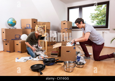 Young couple, just  moved into a new apartment. Unpacking moving boxes. - Stock Photo