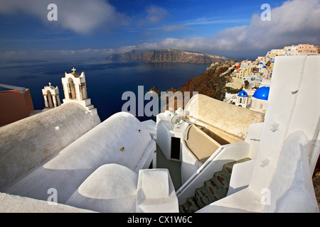 Santorini island, wide angle view of picturesque Oia village, hanging over the caldera. In the background, Thirasia - Stock Photo