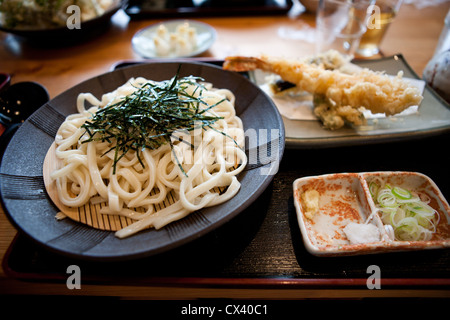 Traditional cold udon noodles served with shrimp tempura on the side. - Stock Photo